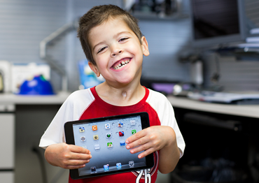 Young boy holding an iPad